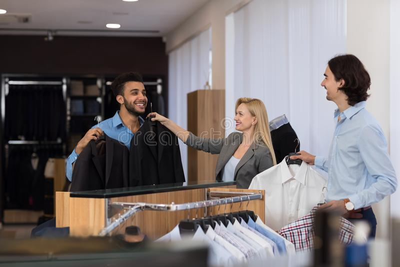 Female Shop Assistant Help Young Handsome Business Man Choose Suit In Clothes Shop, Businessmen In Luxury Clothing Store royalty free stock photos