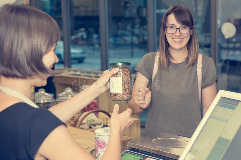 Female shop assistant serving a customer at a desk. royalty free stock photos