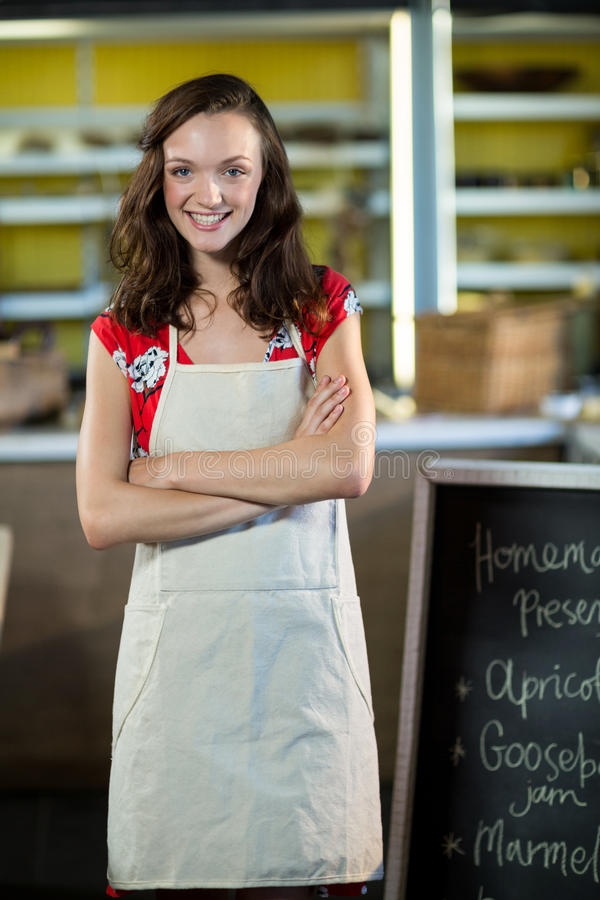 Female shop assistant standing besides menu chalk board with her arms crossed. Portrait of a female shop assistant standing besides menu chalk board with her royalty free stock images