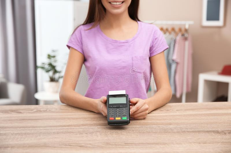 Female shop assistant with terminal for contactless payment at counter royalty free stock images