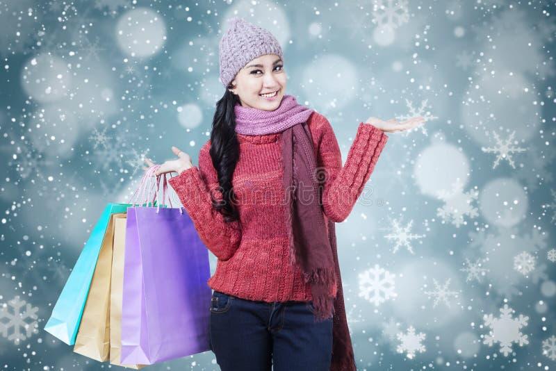Female shopaholic with snowflake background stock image