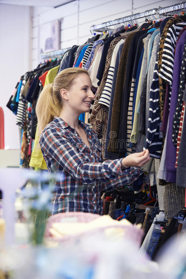 Female Shopper In Thrift Store Looking At Clothes. Shopper In Thrift Store Looking At Clothes stock images