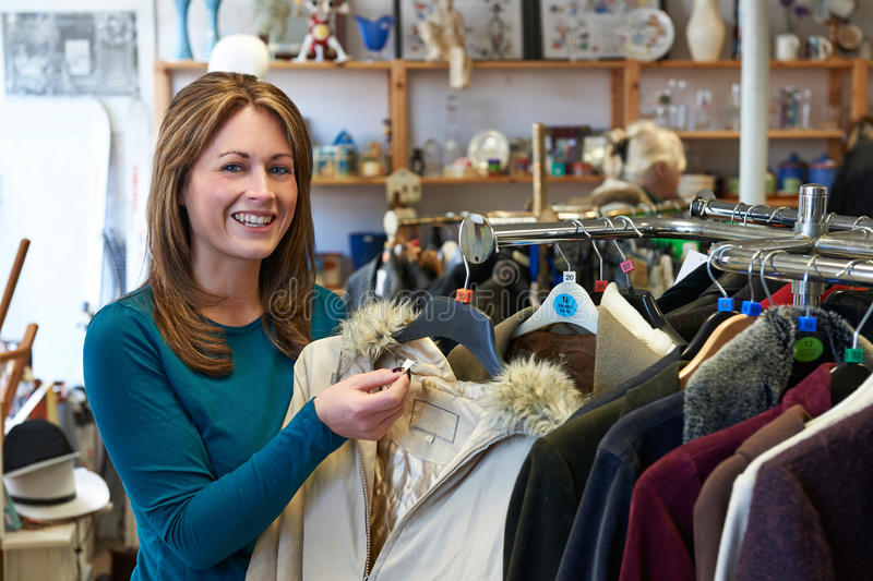 Female Shopper In Thrift Store Looking At Clothes. Female Shopper In Thrift Store Looks At Clothes royalty free stock photo