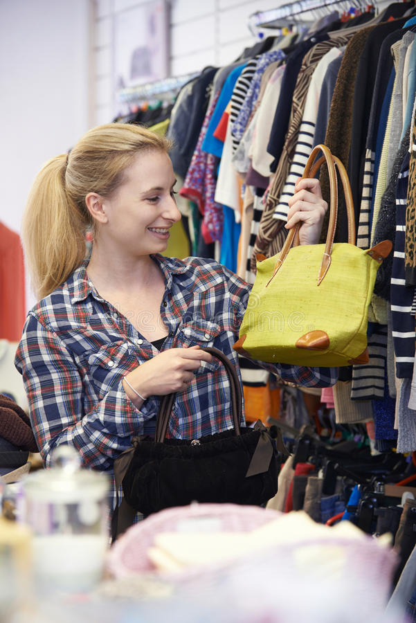 Female Shopper In Thrift Store Looking At Handbags. Shopper In Thrift Store Looking At Handbags stock photography