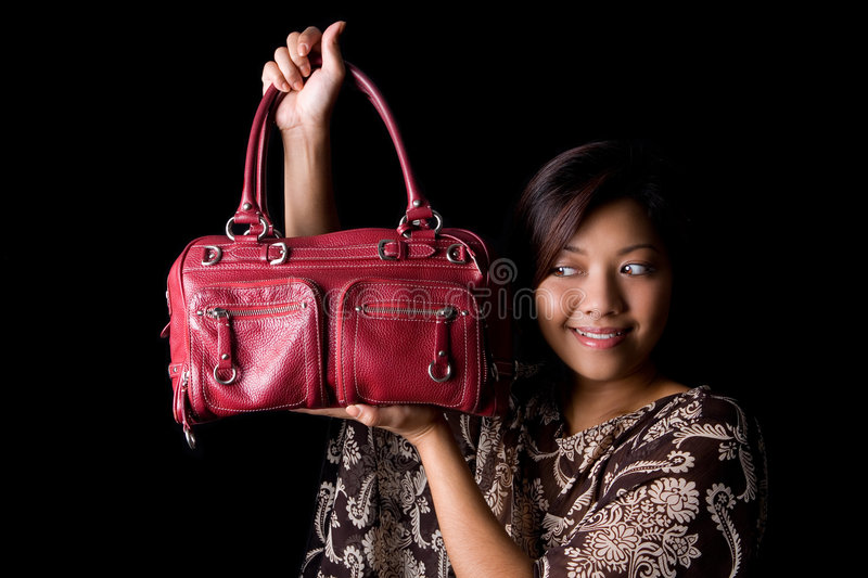 Female showing off her new red leather handbag. stock photography