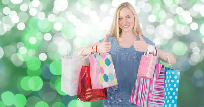 Female showing thumbs up while carrying colorful shopping bags royalty free stock photo