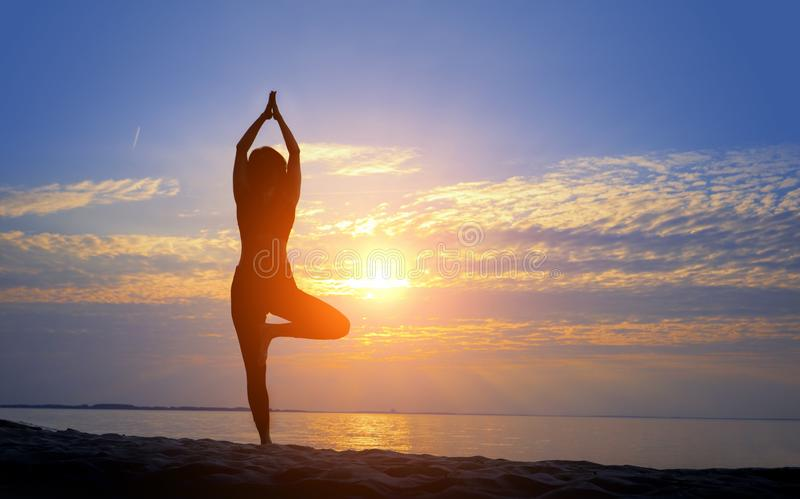 Female silhouette doing yoga asana at sunrise with hands raised to sun stock images