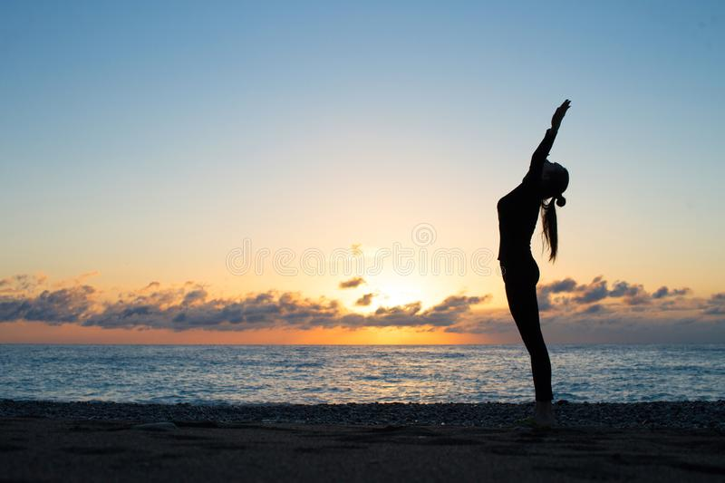 Female silhouette greeting to the rising sun on the beach in the morning. Human silhouette doing yoga on the beach at the dawn. Woman rise her hands up and royalty free stock image