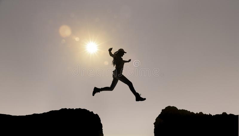 Female Silhouette Jumping over canyon stock image