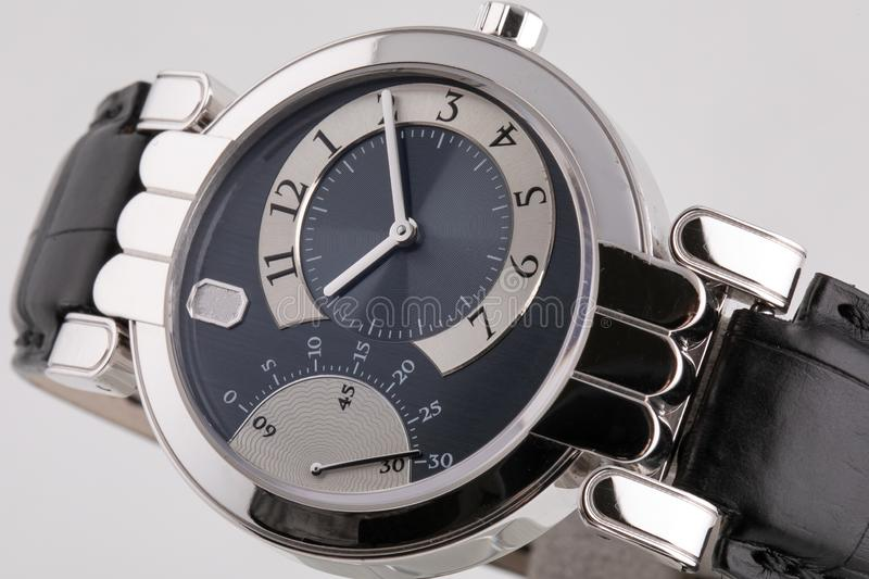 Female silver watch with a black dial, silver clockwise, stopwatch with a black leather strap. royalty free stock images