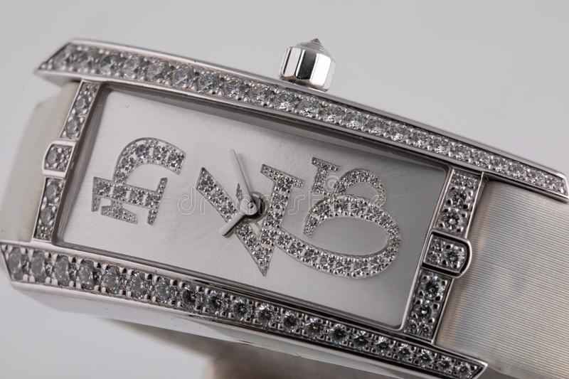 Female silver watch with a grey dial, silver clockwise, framing of the stones, with a white cloth strap stock photos