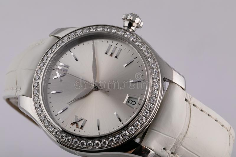 Female silver watch with a light grey dial, silver clockwise, chronograph, with a white leather strap isolated on white background royalty free stock photography