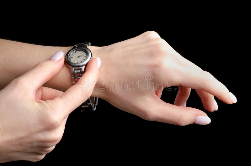 Female silver wrist mechanical watch in hand. On a black background isolation stock photo
