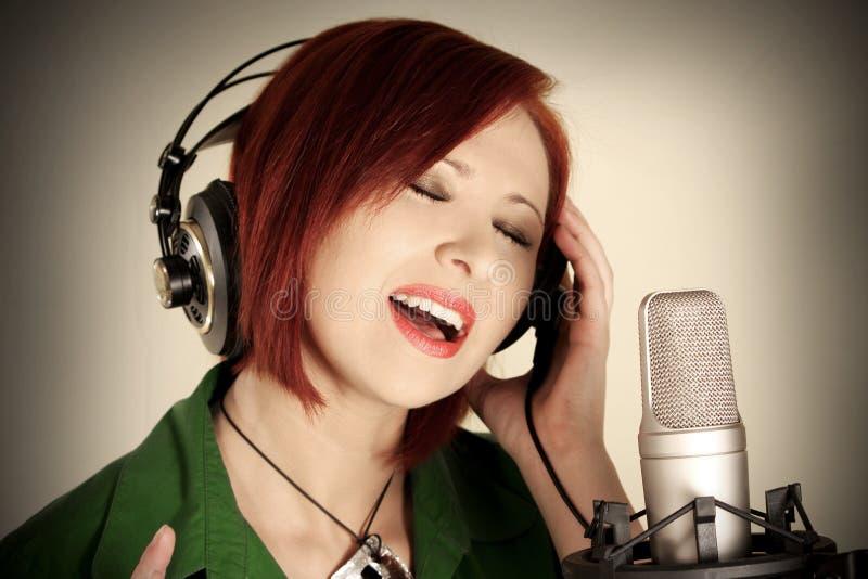 Female singer. With headphones recording in studio stock photos