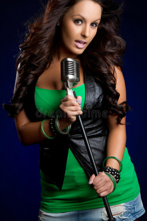 Female Singer. Beautiful young female microphone singer royalty free stock photos