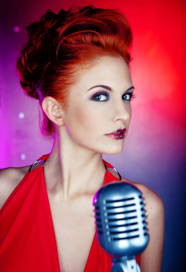 Female singer. Red dress with retro mic stock images