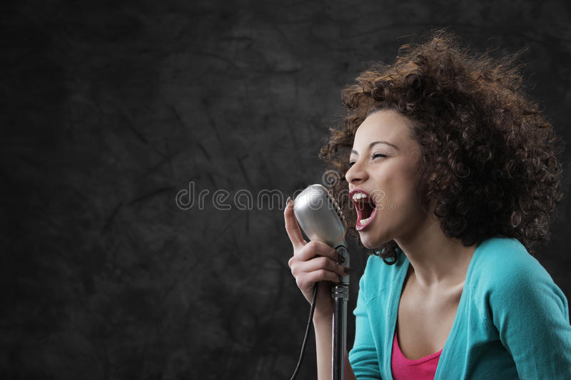 Female singer. Young female singer with brown curly hair singing a song royalty free stock images