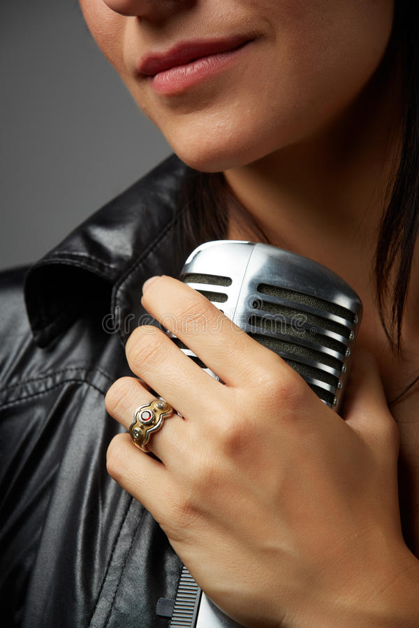 Female Singer. Young adult caucasian female singer with red lips and wearing a black leather jacket holding an old style microphone in her left hand - closeup stock photography