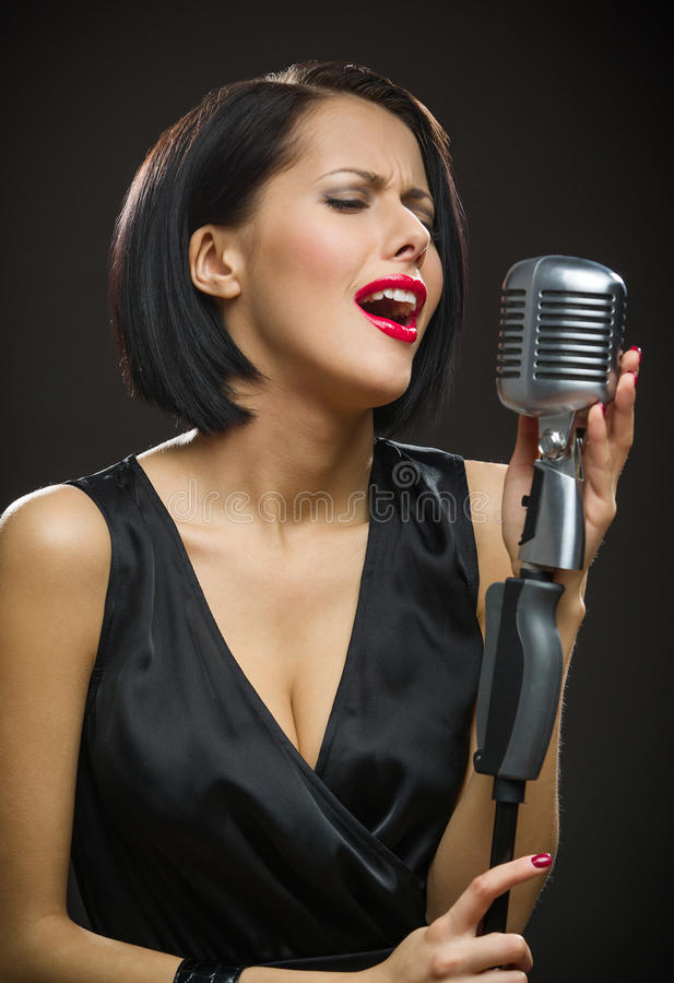 Female singer with closed eyes keeping microphone. Half-length portrait of female singer with closed eyes wearing black evening dress and keeping microphone on stock photo