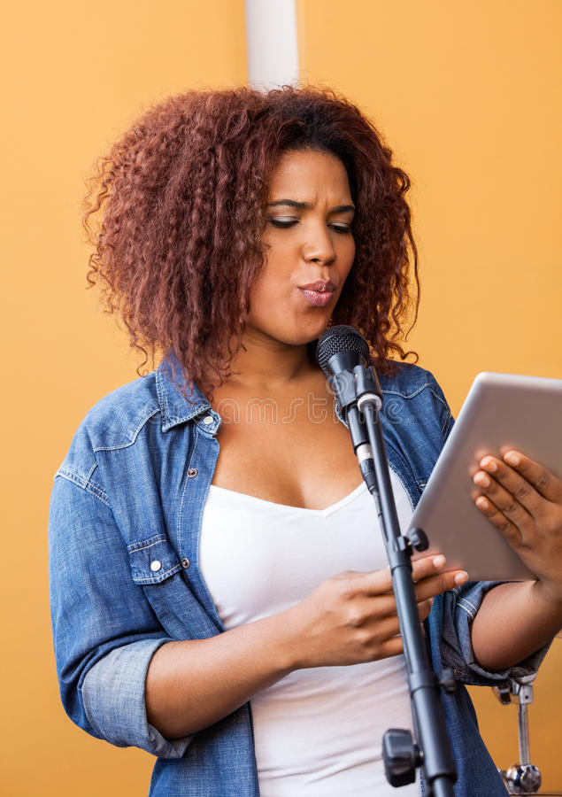 Female Singer Holding Digital Tablet While. Young female singer holding digital tablet while performing in recording studio royalty free stock images