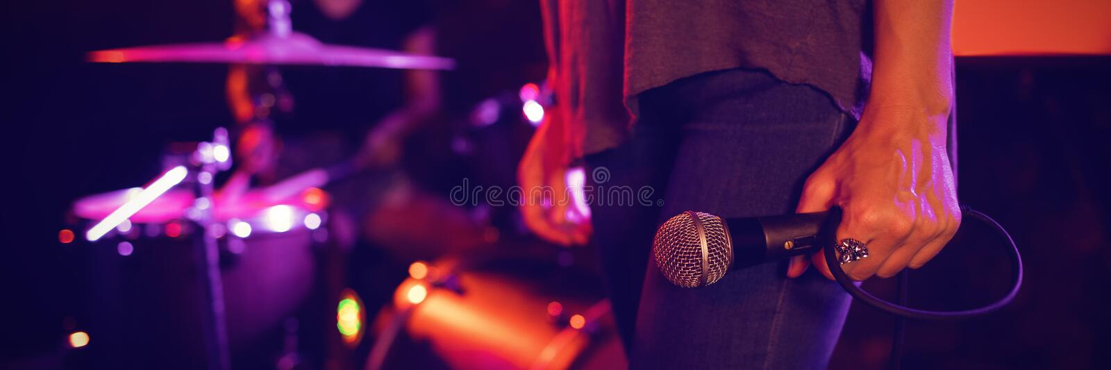 Female singer holding microphone with drummer performing in illuminated nightclub royalty free stock photography