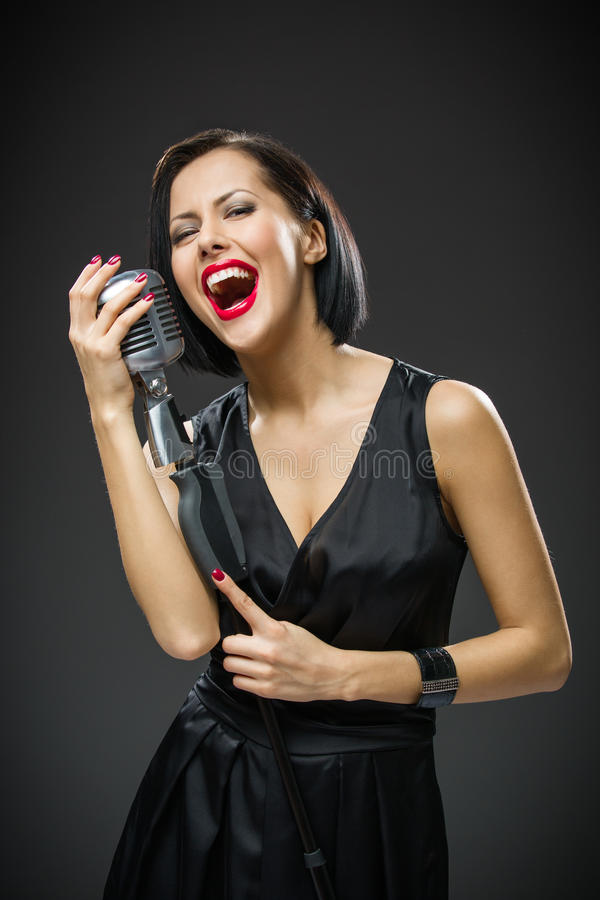Female singer keeping mike. Half-length portrait of female musician wearing black evening dress and keeping mike on grey background. Concept of music and retro stock image