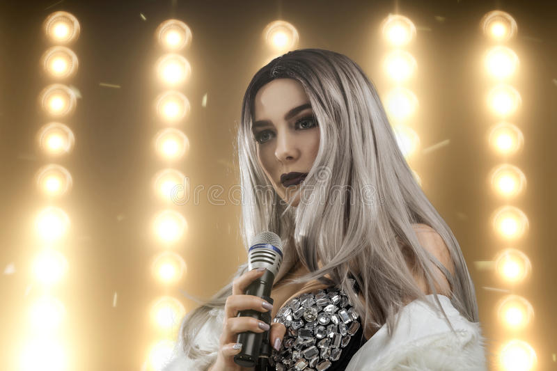 Female singer with lights on background royalty free stock photos
