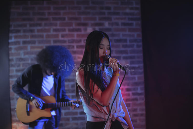 Female singer with male guitarist performing at music concert. Confident female singer with male guitarist performing at music concert stock image
