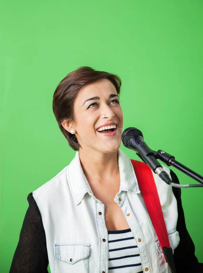 Female Singer Performing Against Green Wall. Happy female singer performing against green wall in recording studio royalty free stock photography