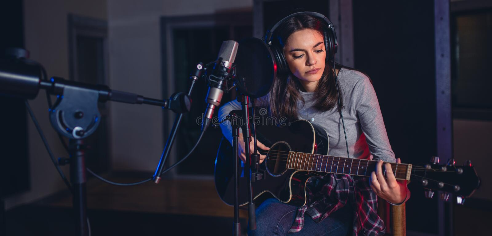Female singer performing a song in studio. And playing guitar. Woman vocal artist playing guitar in a recording studio royalty free stock images
