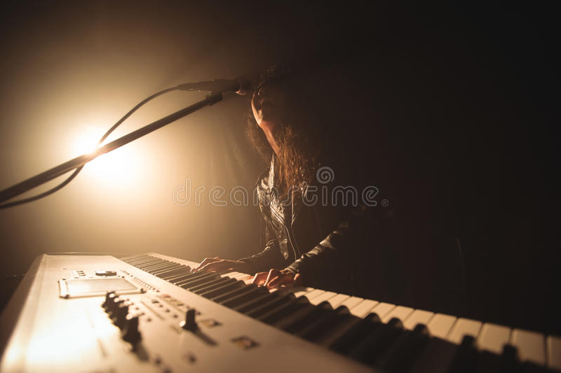 Female singer playing piano while performing in music concert. Low angle view female singer playing piano while performing in music concert stock photography