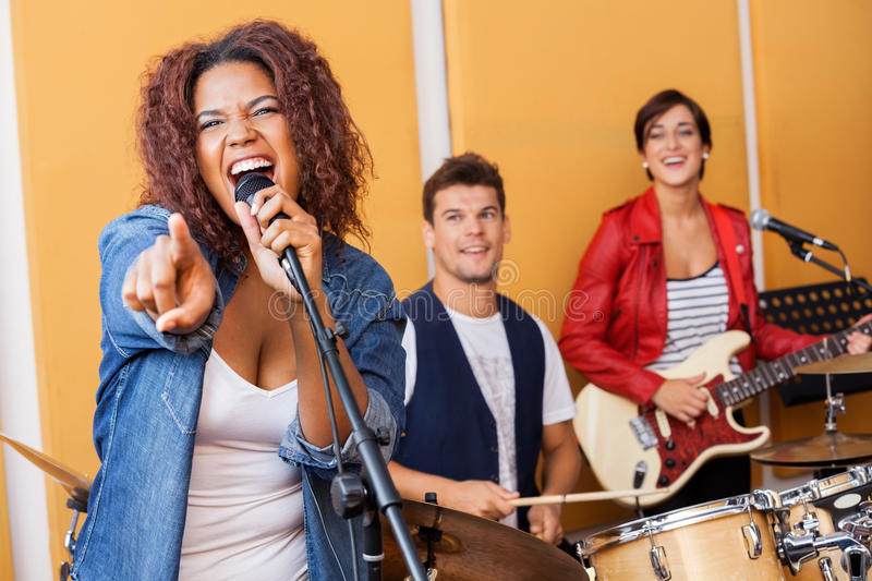 Female Singer Pointing While Performing In royalty free stock photography