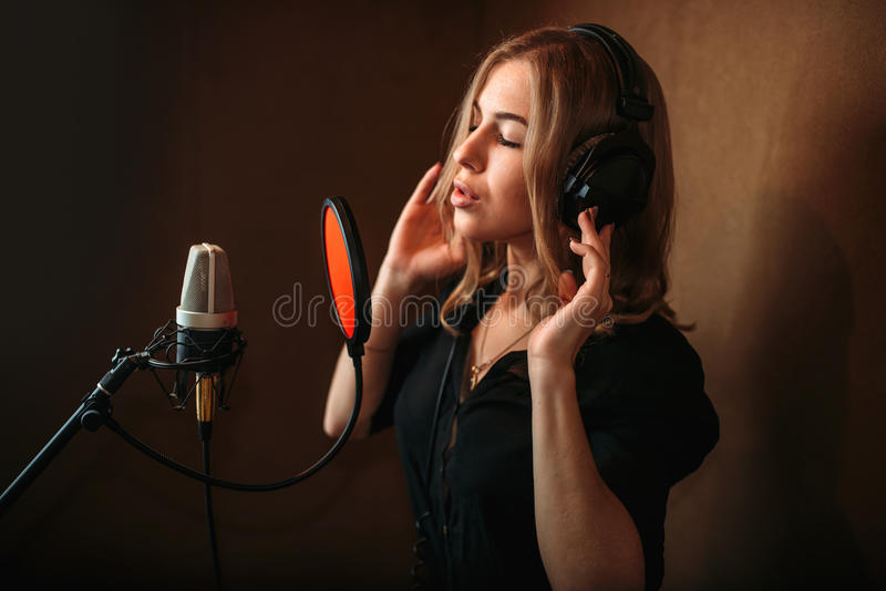 Female singer recording a song in music studio. Woman vocalist in headphones against microphone. Audio recording. Professional digital sound technologies royalty free stock image