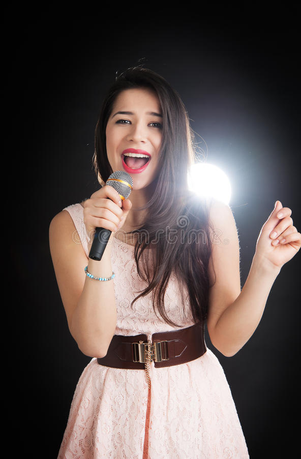 Female singer sings into a microphone. On a black background royalty free stock photography