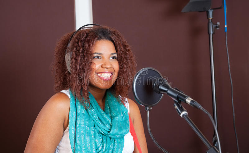 Female Singer Smiling While Performing In Studio. Young female singer smiling while performing in recording studio royalty free stock photography