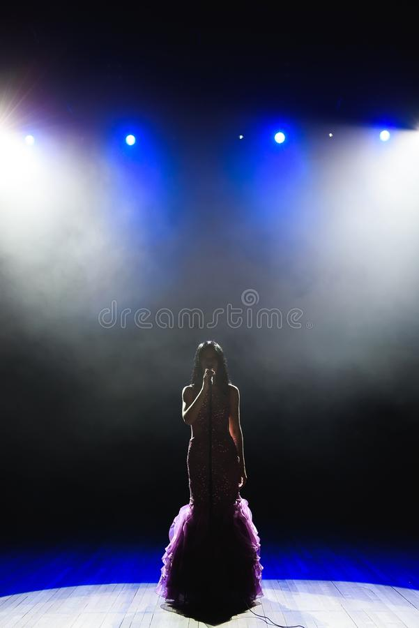 Female singer on the stage holding a microphone. stock photography