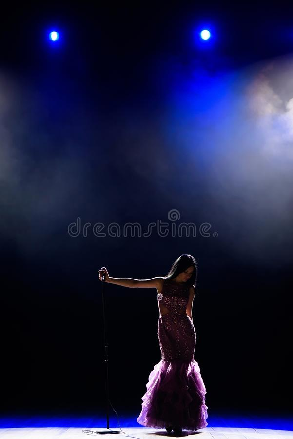 Female singer on the stage holding a microphone. stock photo