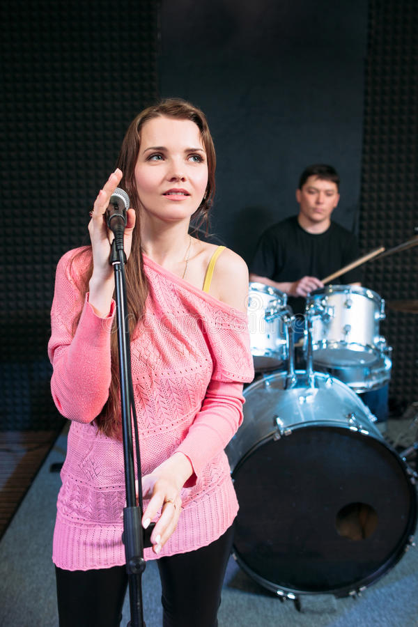Female singer on stage holding microphone royalty free stock photo