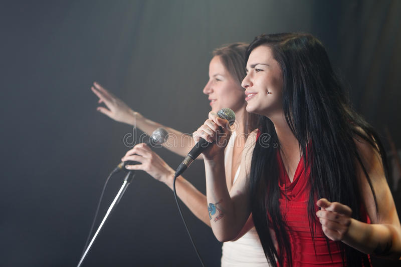 Female singers. Performing on stage royalty free stock photos