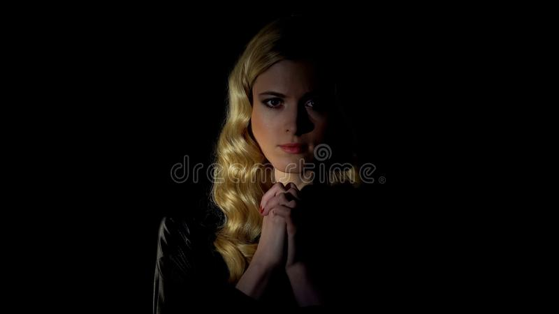 Female sinner praying in dark room, looking for forgiveness, faith and belief. Stock photo royalty free stock photography