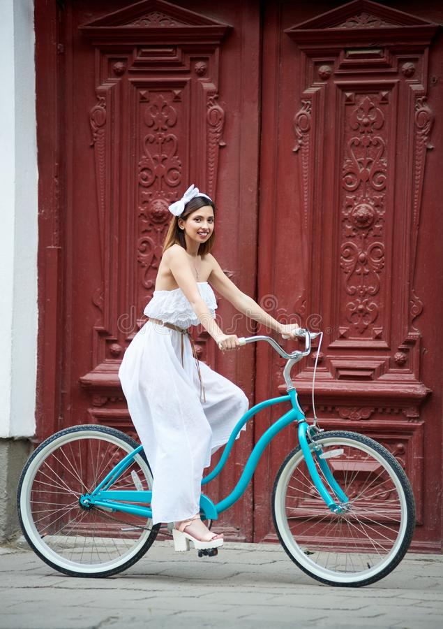 Female sits on bicycle against on background old red door royalty free stock photos