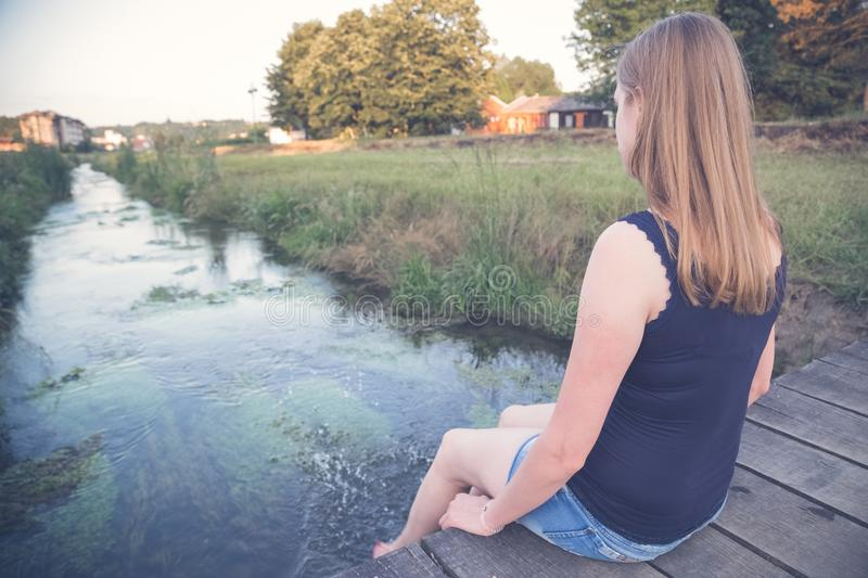 Female sitting on small wooden bridge with her legs in stream. P royalty free stock image