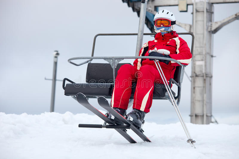 Female skier on chair-lift. Female skier in red sportswear on a chair-lift royalty free stock image