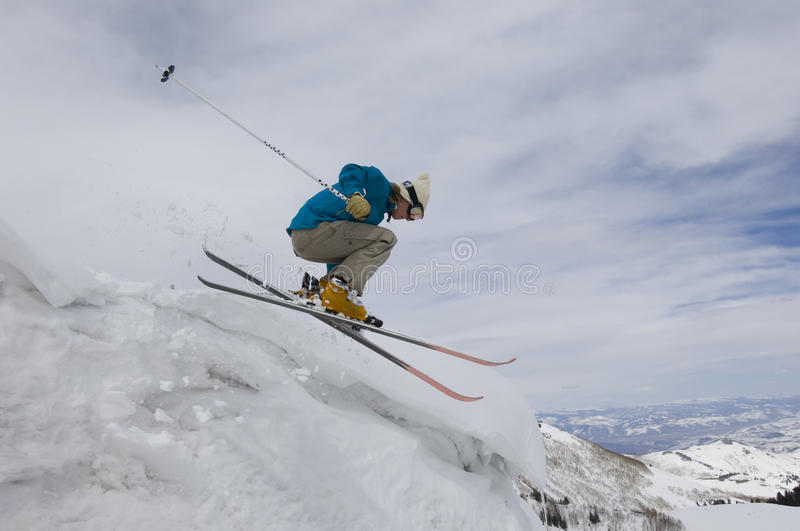 Female Skier Jumping Off Icy Overhang royalty free stock image