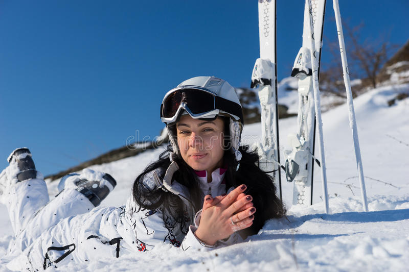 Female Skier Lying on Snow Covered Mountainside royalty free stock photography