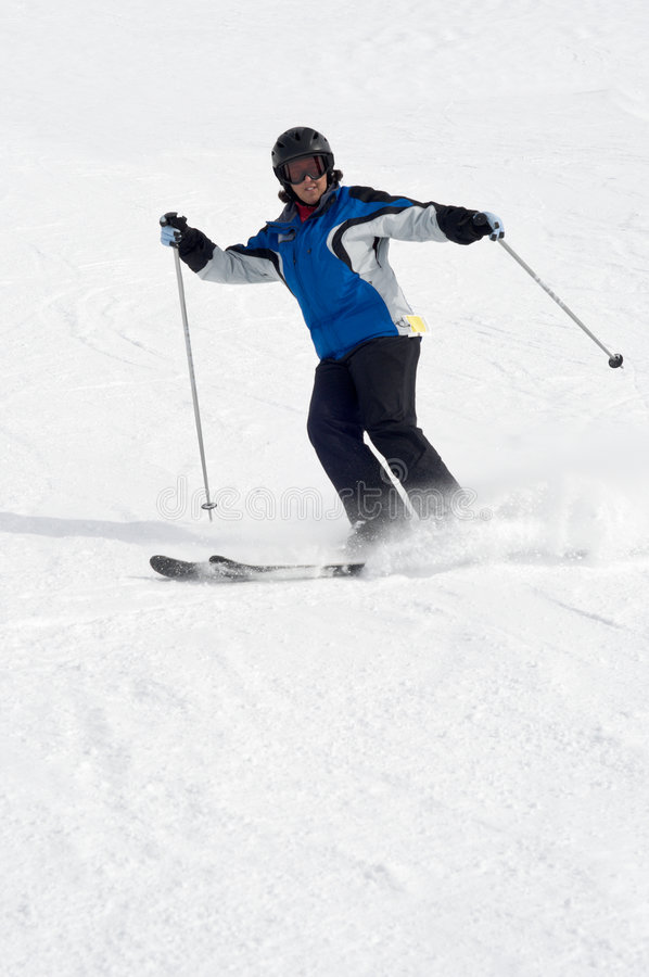 Female skier on ski trail, cloud of powder snow royalty free stock photography