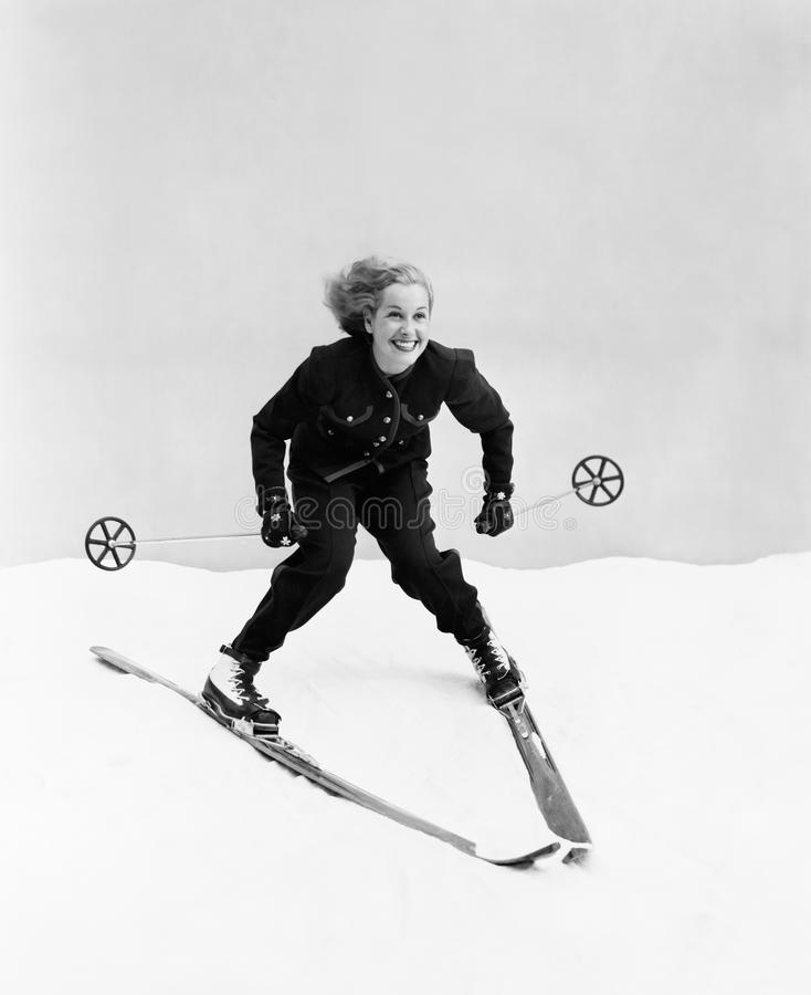 Female skier skiing downhill royalty free stock photos