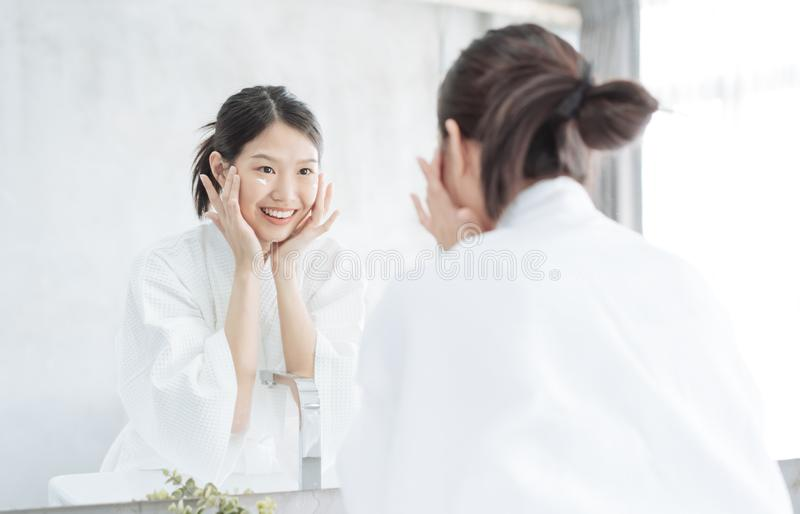 Female Skin Care. Young asian woman touching her face and looking to mirror in bathroom. stock photo