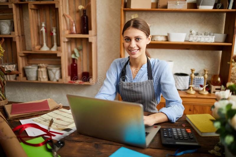 Female Small Business Owner. Portrait of female small business owner using laptop and looking at camera in shop, copy space royalty free stock photography