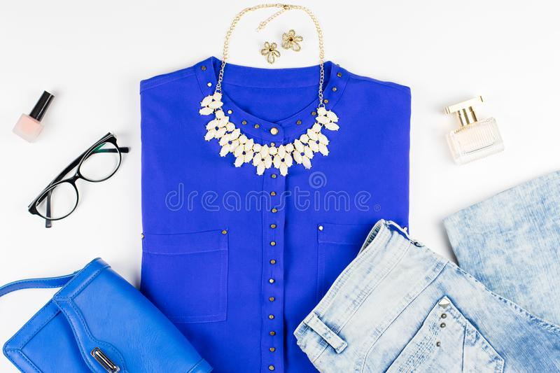 Female smart casual style clothing and accessories -purple shirt, handbag, make up items. Top view royalty free stock photography